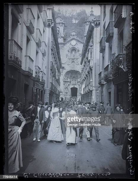 View of pedestrian traffic on the Calle de la Trinidad with the main entrance to the Basilica of Santa Maria del Coro visible at the end of the...