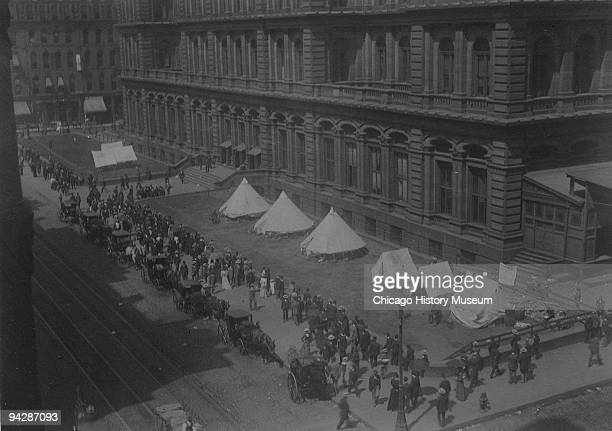 View of pedestrians and carriages on the sidewalk and the troops and tents camped on the courthouse grounds during the Pullman railroad Strike...