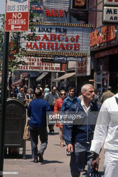 View of pedestrians as they walk along 42nd street past a row of cinemas that advertise pornographic films in Manhattan's Times Square New York New...