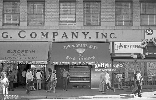 View of pedestrians as they walk past store fronts several of them gated shut on a street of midtown Manhattan New York New York September 1980