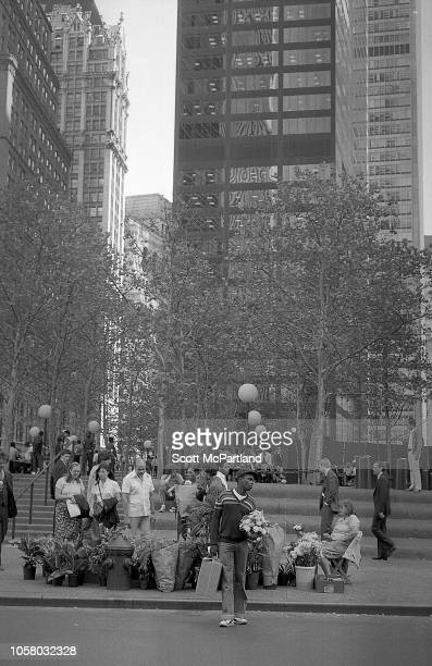 View of pedestrians in front of Liberty Plaza Park New York New York September 1980 A man with a bouquet of flowers stands in the street while behind...