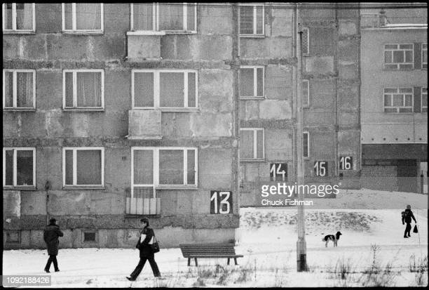 View of pedestrians in the snow outside a series of numbered apartment buildings in the industrial suburb of Nowa Huta Krakow Poland December 1978