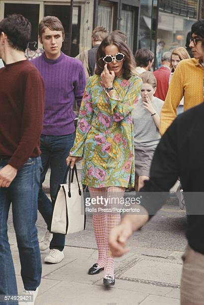 View of pedestrians including a young girl wearing a mini dress with a floral motif and sunglasses walking along the Kings Road in Chelsea London...
