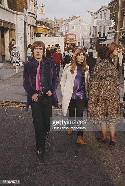 View of pedestrians including a young man wearing a purple velvet jacket and pink tie and a young woman wearing a white fur style coat walking down...