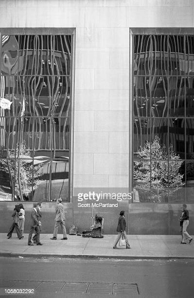 View of pedestrians on an unspecific sidewalk New York New York September 1980 At center a street musician reaches into his guitar case