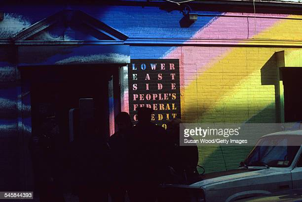 View of pedestrians outside the rainbowdecorated exterior of the Lower East Side People's Credit Union New York New York February 1988