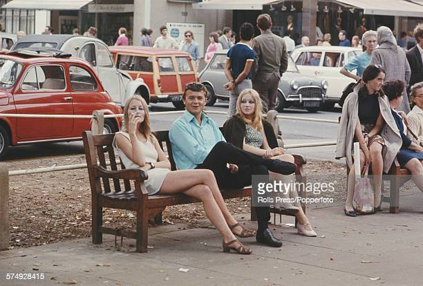 View of pedestrians passing three young people including two young girls wearing mini skirts and smoking cigarettes sitting on a bench on the Kings...