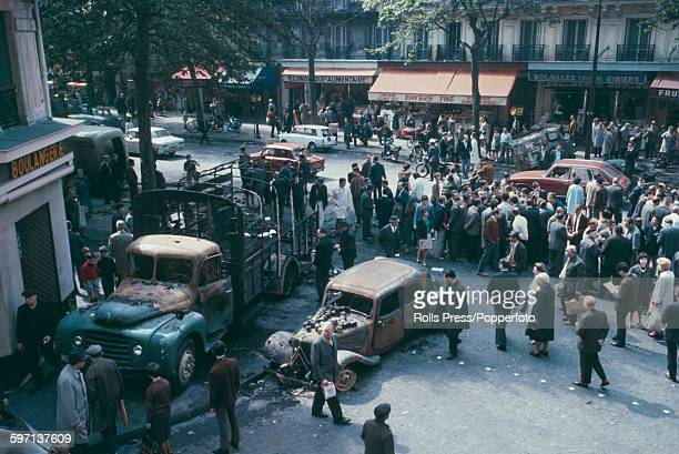 View of pedestrians walking past and inspecting a burnt out and wrecked citroen car and truck on Boulevard SaintGermain in Paris in the aftermath...