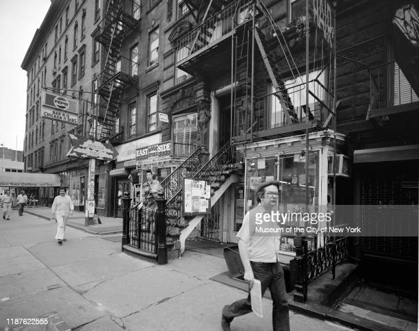 View of pedestrians walking past the East Side Bookstore at 34 Saint Mark's Place in the East Village neighborhood, New York, New York, circa 1975.