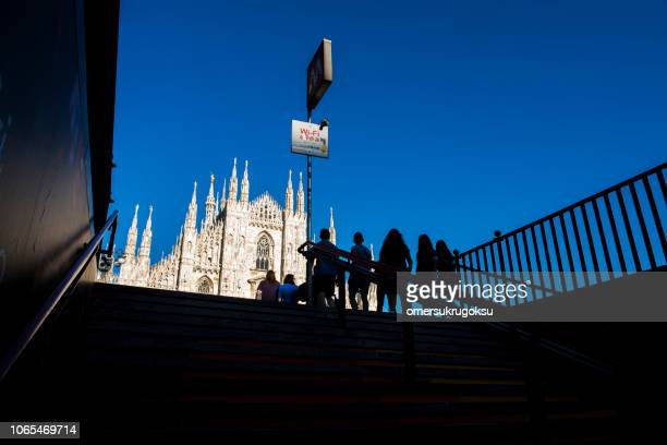 view of people and the duomo di milano (mariae nascenti) from the stairs at the metro exit in milan, italy - duomo di milano foto e immagini stock