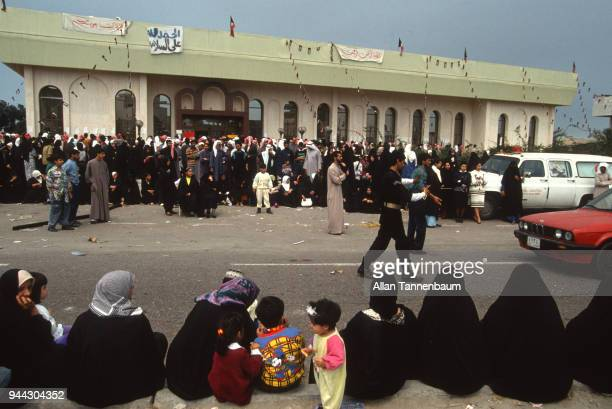 View of people as they line the street and wait for the arrival of repatriated Kuwaiti Prisoners of War during the Gulf War Kuwait 1991