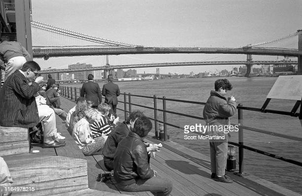 View of people as they sit and stand on the back deck of the South Street Seaport, New York, New York, March 3, 1988. Visible in the background are...