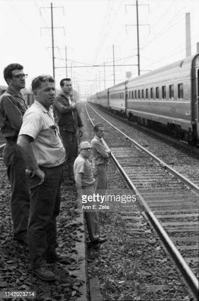 View of people as they stand beside the train tracks as Robert F Kennedy's funeral train approaches, Elizabeth, New Jersey, June 8, 1968. One man...
