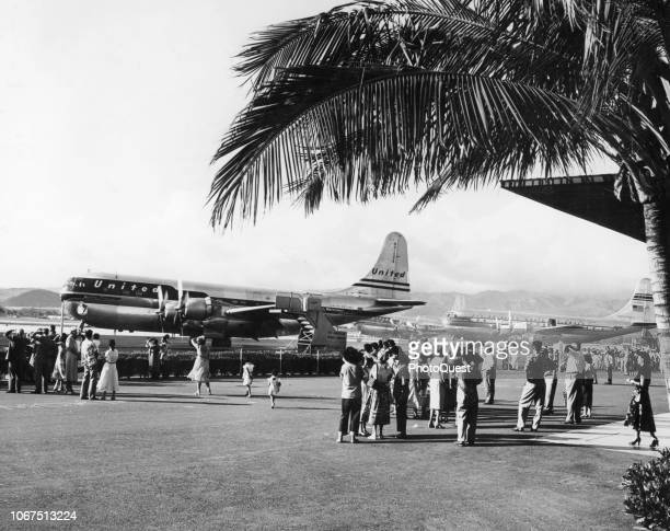 View of people as they stand outside and watch planes at Honolulu International Airport Honolulu Hawaii 1951 In the foreground is a United Aitlines...