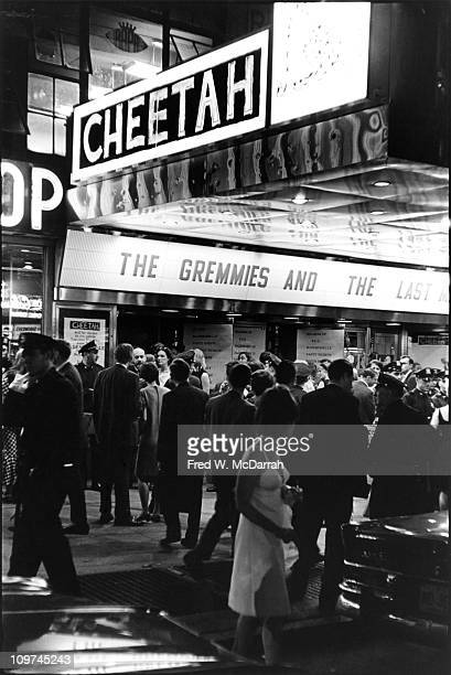 View of people crowded under the marquee of the Cheetah club which advertises a performance by the Gremmies though signs on the door refer to a...