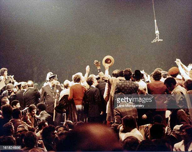 View of people crowding around the ring at the end of the boxing match between American heavyweights boxer Muhammad Ali and Joe Frazier at Madison...
