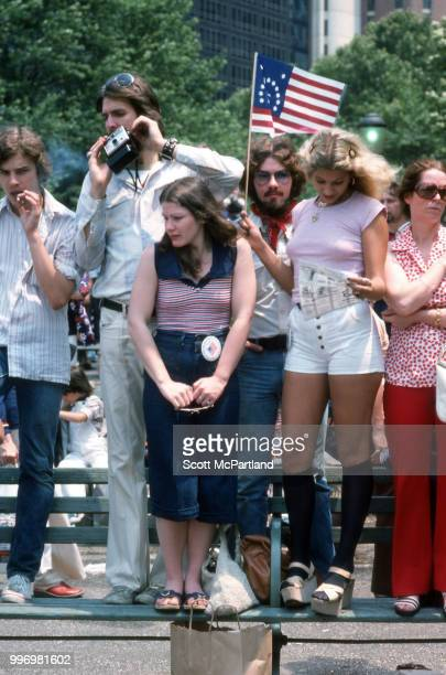 View of people gathered in downtown Manhattan as they stand on a park bench during the bicentennial celebrations New York New York July 4 1976 They...