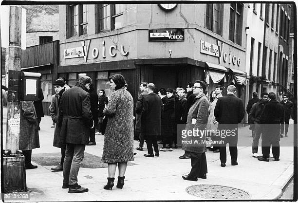 View of people gathered outside the offices of the Village Voice newspaper on Sheridan Square as they wait for the latest edition New York New York...
