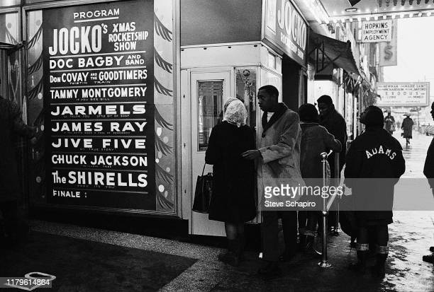 View of people line up to purchase tickets at the Apollo Theater box office window, New York, New York, 1961. A poster advertises performances by the...