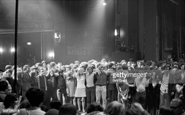 View of people many their arms over one another's shoulders as they stand on stage at the Filmore East during the venue's takeover by anarchist...