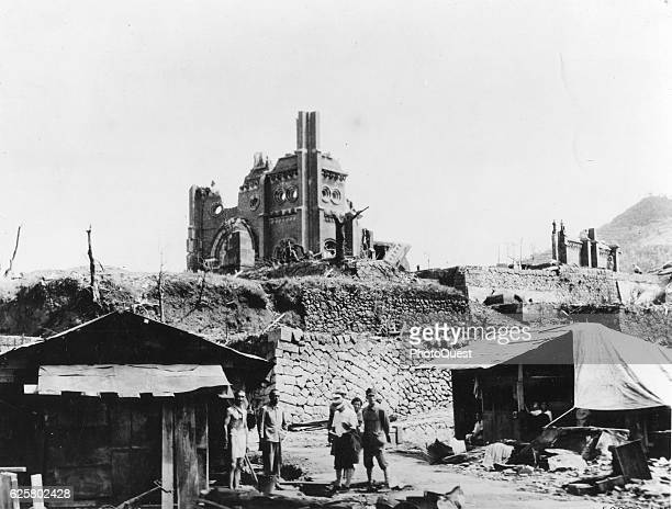 View of people outside ramshackle shanties in the rubble following the US bombing Nagasaki Japan 1948