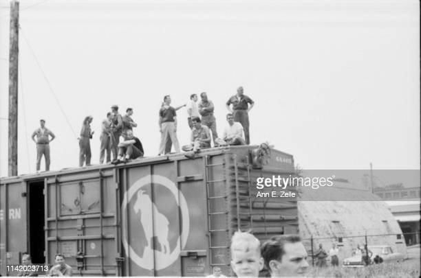 View of people perched atop a boxcar as they wait for Robert F Kennedy's funeral train, Elizabeth, New Jersey, June 8, 1968.