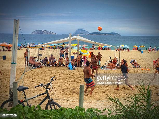 view of people playing volleyball on beach - beach volleyball stock pictures, royalty-free photos & images
