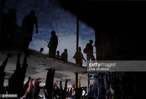 TOPSHOT View of people queuing to vote outside Rocinha favela during general elections in Rio de Janeiro Brazil on October 7 2018 Brazilians began...
