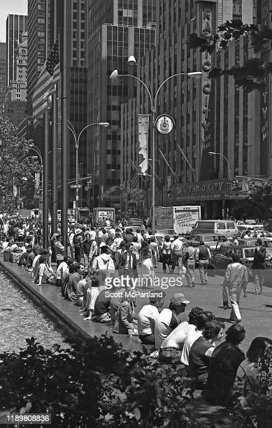 View of people seated around a fountain , as well as pedestrians, on 6th Avenue , New York, New York, May 25, 1984. Visible across the street is...