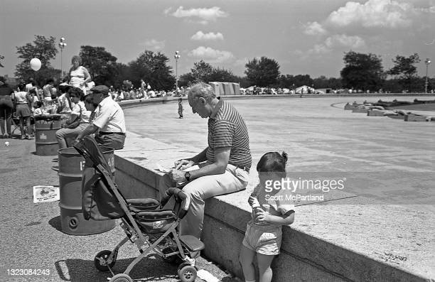 View of people sitting along the stone wall next to the unisphere in Flushing Meadows Park, in the Corona neighborhood, Queens, New York, New York,...