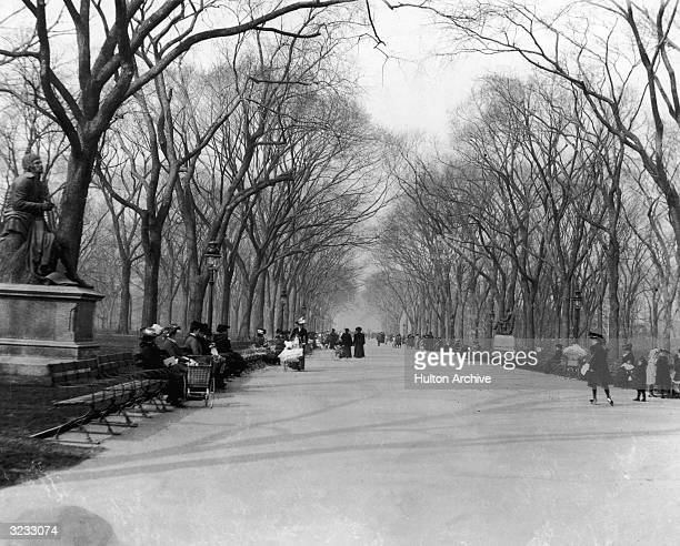 A view of people sitting and strolling along the paved mall in Central Park with bare trees flanking the road New York City There are statues...