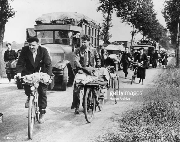 View of people walking driving and riding bicycles with their belongings during the evacuation of Paris following the German invasion of France