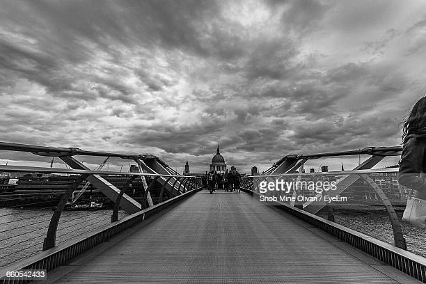 View Of People Walking On Bridge Under Cloudy Sky