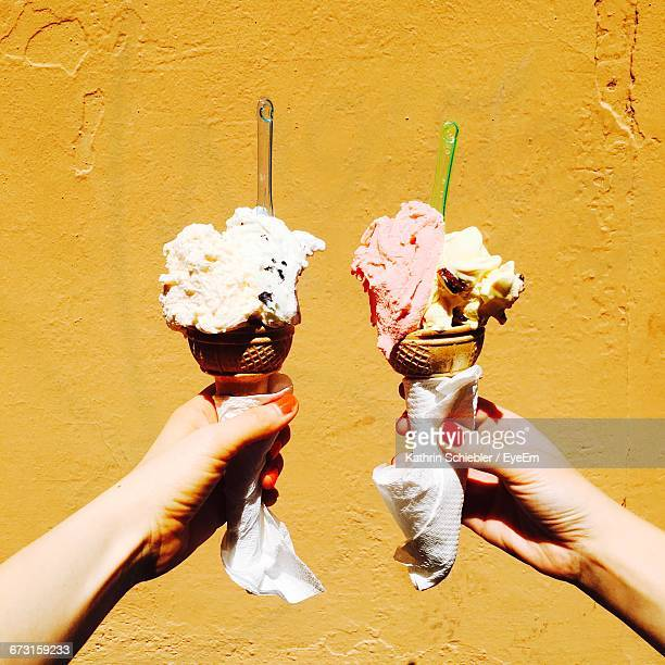 view of person holding ice cream cone in front of wall - ice cream cone stock pictures, royalty-free photos & images