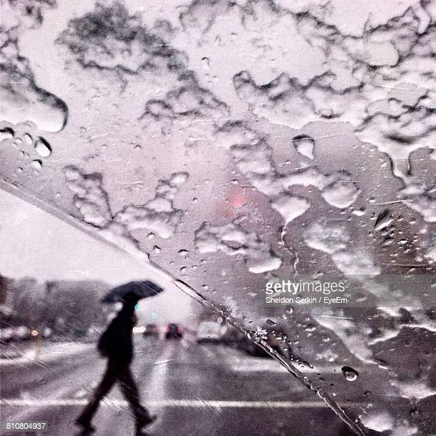 View of person walking on street seen through wet window glass