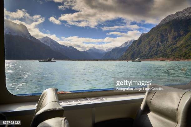 a view of peulla from the catamaran window during the winter andean lake crossing - azul turquesa stockfoto's en -beelden