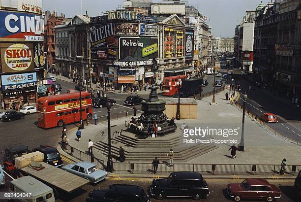 View of Piccadilly Circus in London with cars buses and traffic passing the Shaftesbury Memorial fountain and statue of Eros in May 1971 Neon lit...