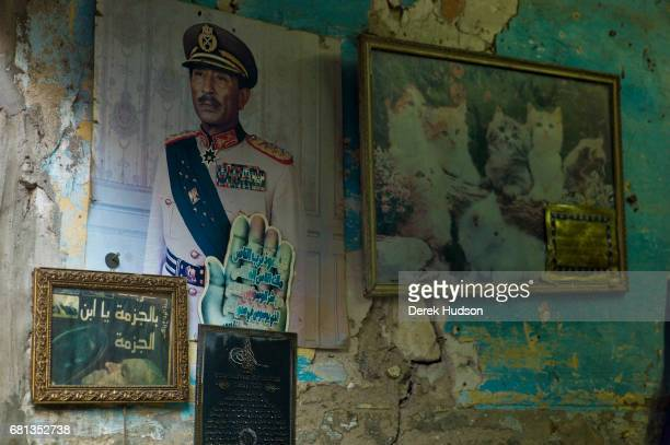 View of pictures posters and advertisements on the deteriorating wall of an antique shop Alexandria Egypt December 12 2009 Among the pictures are a...