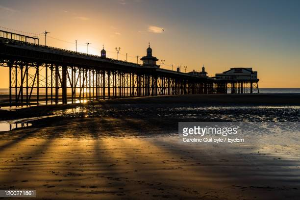 view of pier on beach during sunset - lancashire stock pictures, royalty-free photos & images