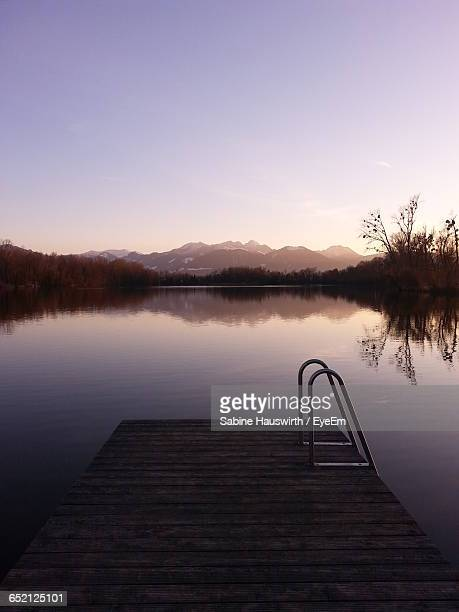 view of pier on calm lake - sabine hauswirth stock pictures, royalty-free photos & images