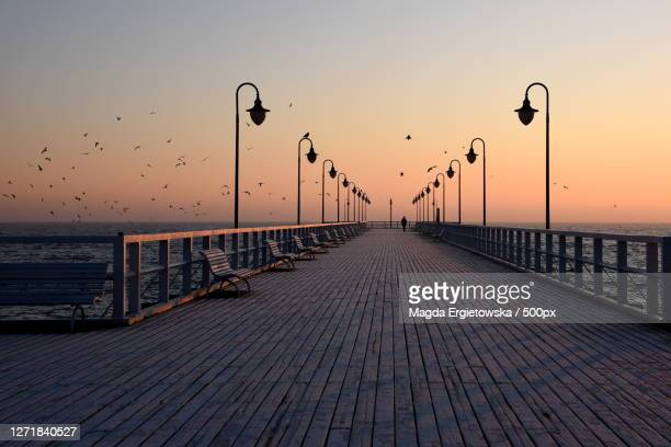 view of pier over sea against sky during sunset, sopot, poland - jetty stock pictures, royalty-free photos & images