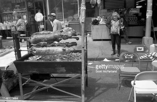 View of pigs as they are roasted over coals in front of a grocery and meat market in Hell's Kitchen during an International Food Festival New York...