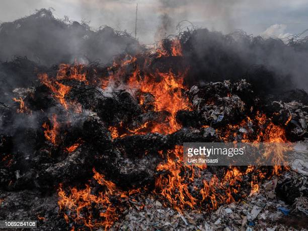 View of plastic waste being burnt at a import plastic waste dump in Mojokerto on December 4, 2018 in Mojokerto, East Java, Indonesia. Indonesia's...