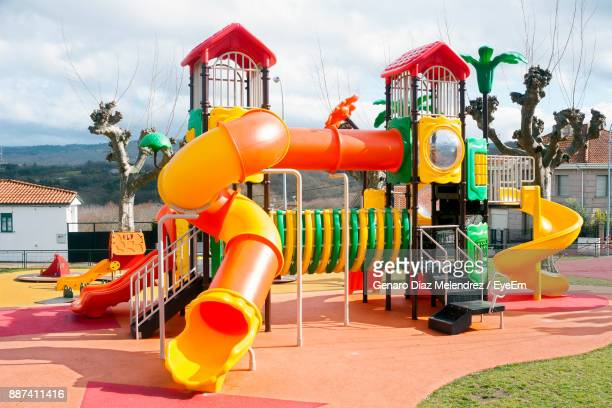 view of playground against cloudy sky - spielgerät stock-fotos und bilder