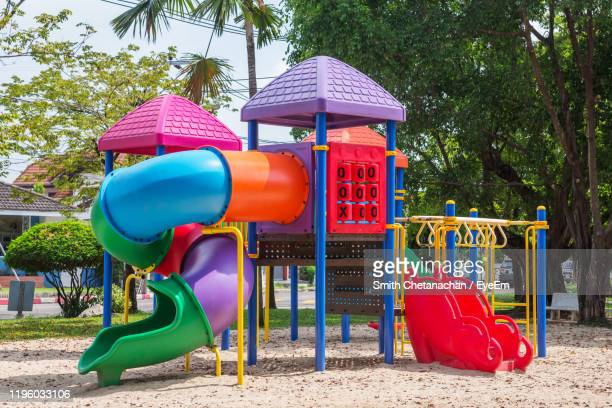 view of playground against trees in park - slide play equipment stock pictures, royalty-free photos & images