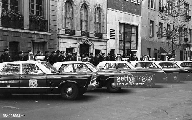View of police officers and patrol cars lining the street during an antiViet Nam War demonstration New York New York October 17 1965