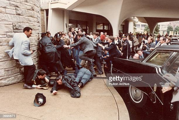 Police and Secret Service agents diving to protect American President Ronald Reagan amid a panicked crowd during an assassination attempt by John...