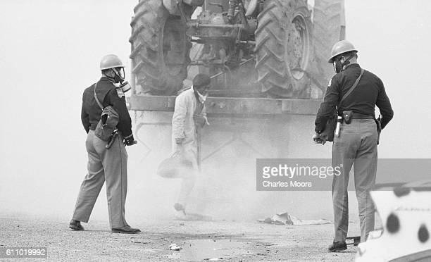 View of police officers in a gas masks and a Civil Rights marcher in a cloud of tear gas at the base of the Edmund Pettus Bridge during the first...