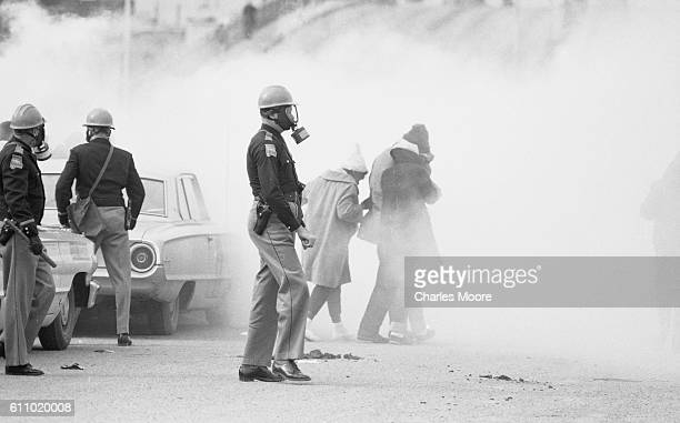 View of police officers in a gas masks and Civil Rights marchers in a cloud of tear gas at the base of the Edmund Pettus Bridge during the first...