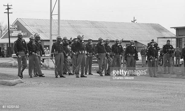 View of police officers in gas masks lined up across Broad Street at the base of the Edmund Pettus Bridge to stop the first Selma to Montgomery...